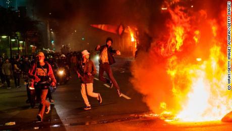 Un manifestant jette un cône de signalisation sur un feu jeudi à Jakarta.
