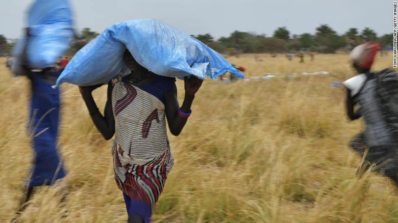Villagers collect food aid dropped from a World Food Programme plane to a village in Ayod county, South Sudan, in February 2020.