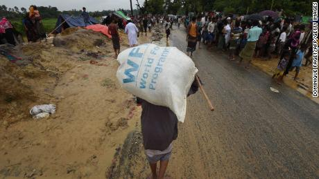 A Rohingya Muslim refugee carries a WFP rice bag along a road in Bangladesh in September 2017.