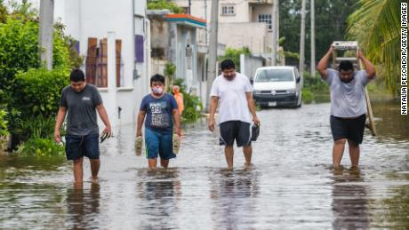 People walk on a flooded street after Hurricane Delta hit near Cozumel on October 07, 2020 in Cozumel, Mexico.