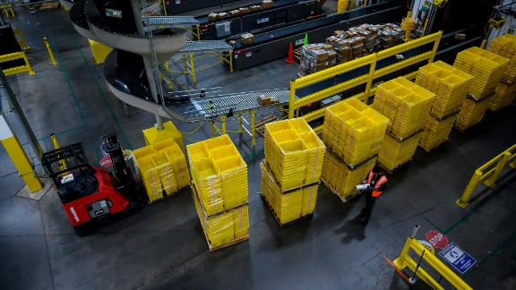 A man works at a distribution station at the 855,000-square-foot Amazon fulfillment center in Staten Island, one of the five boroughs of New York City, on February 5, 2019. - Inside a huge warehouse on Staten Island thousands of robots are busy distributing thousands of items sold by the giant of online sales, Amazon. (Photo by Johannes Eisele/AFP/Getty Images)