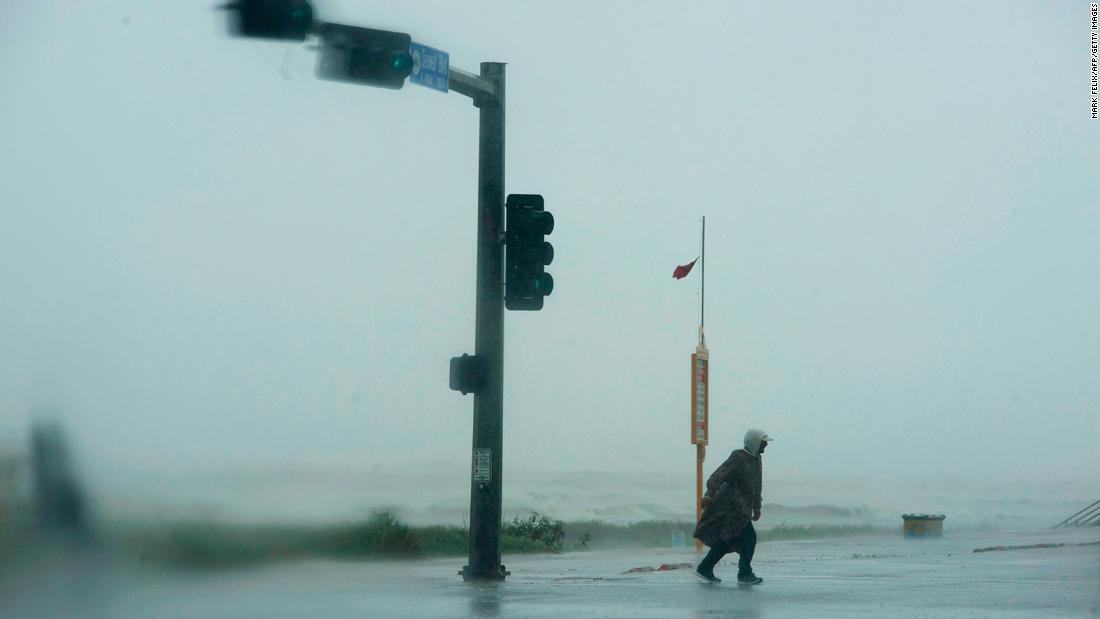 A man walks across the street as the outer bands of Hurricane Delta lash Galveston, Texas, on October 9.