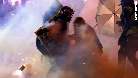 Protesters withdraw after police used tear gas on Friday, October 9, 2020 in Wauwatosa, Wisconsin.