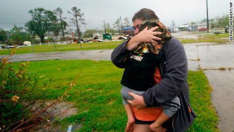 Danielle Fontenot runs to a relative's home with her son Hunter in the Hurricane Delta rain on Friday, October 9, 2020 in Lake Charles, Louisiana.