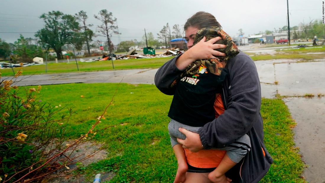 Danielle Fontenot runs to a relative's home in the rain with her son Hunter ahead of Hurricane Delta in Lake Charles, Louisiana, on October 9.