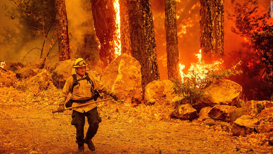 A firefighter walks along a path as the Glass Fire burns in Calistoga, California, on October 1.
