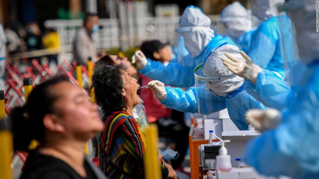 "A health worker takes a swab from a resident at a Covid-19 testing center in Qingdao, China, on October 12. The Chinese port city planned to <a href=""https://edition.cnn.com/2020/10/12/asia/china-qingdao-coronavirus-golden-week-intl-hnk/index.html"" target=""_blank"">test some 9 million people</a> in the following days after 12 locally transmitted cases were reported."