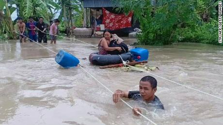 A soldier (front) holds onto a rope as a woman (C) is is pulled to safety through flood waters in a village in Cambodia's western Battambang province on October 10, 2020, following heavy rains in the region. (Photo by STR / AFP) (Photo by STR/AFP via Getty Images)