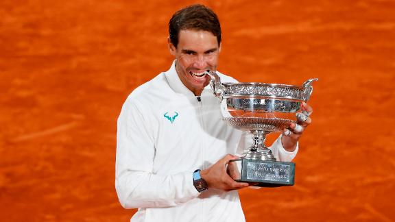 Rafael Nadal of Spain bites the winners trophy following victory in the men's singles final against Novak Djokovic of Serbia in the 2020 French Open at Roland Garros on October 11, 2020 in Paris, France. (Photo by Clive Brunskill/Getty Images)