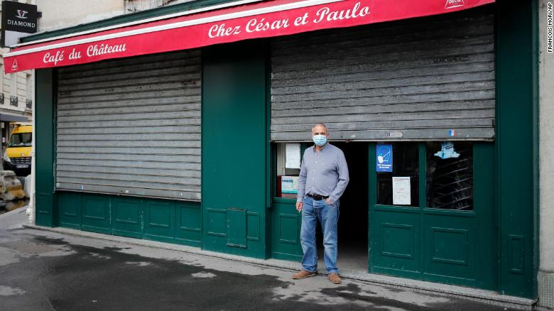 Cesar, from Portugal, stands in front of his bar, in Paris, on October 6, 2020 after all bars in the city were closed under new Covid-19 restrictions.