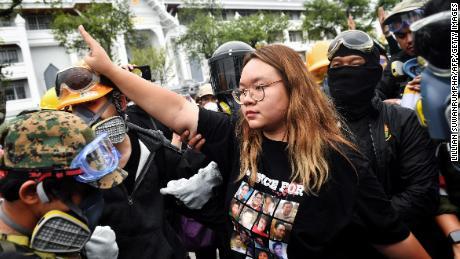 "Protest leader Panusaya ""Rung"" Sithijirawattanakul (C) makes the three-fingered Hunger Games salute during a pro-democracy rally in Bangkok on September 20, 2020."