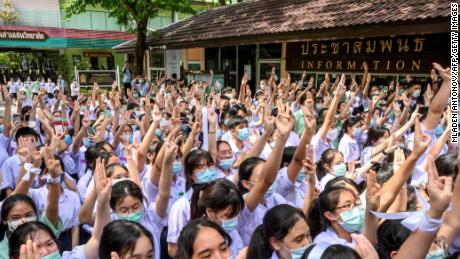 Students make the three-fingered salute at Samsen school to demand for less strict school rules, more tolerance and respect during a protest in Bangkok on October 2, 2020.