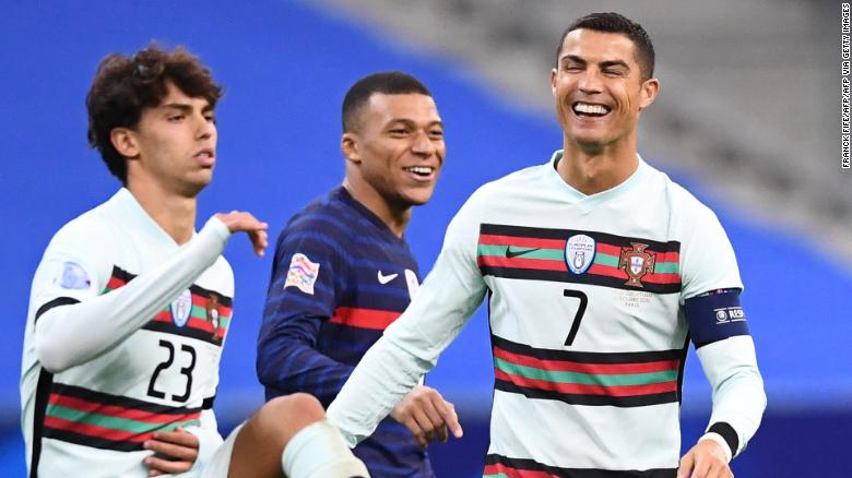 Ronaldo (right) shares a joke with French striker Kylian Mbappe (center) during Portugal's Nations League match.