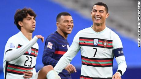 Ronaldo (right) shares a joke with French striker Killian Mbape (center) during Portugal's League of Nations match.
