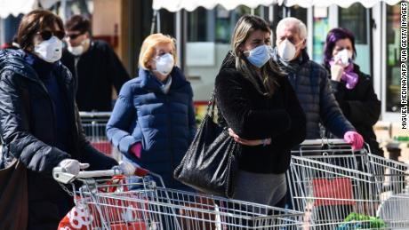 Residents wearing a protective mask wait to do their shopping outside a supermarket in Codogno, southeast of Milan, on March 11, 2020 a day after Italy imposed unprecedented national restrictions on its 60 million people Tuesday to control the deadly COVID-19 coronavirus. (Photo by Miguel MEDINA / AFP) (Photo by MIGUEL MEDINA/AFP via Getty Images)