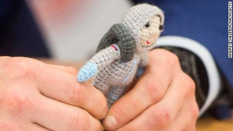 Sergey Kud-Sverchkov holds a knit cosmonaut named Yuri made by his wife Olga, during a press conference prior to his launch.