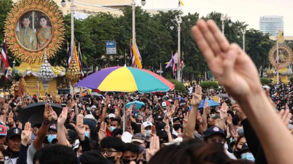Pro-democracy protesters give the three-finger salute as they march towards Government House during an anti-government rally in Bangkok on October 14, 2020. (Photo by Jack TAYLOR / AFP) (Photo by JACK TAYLOR/AFP via Getty Images)