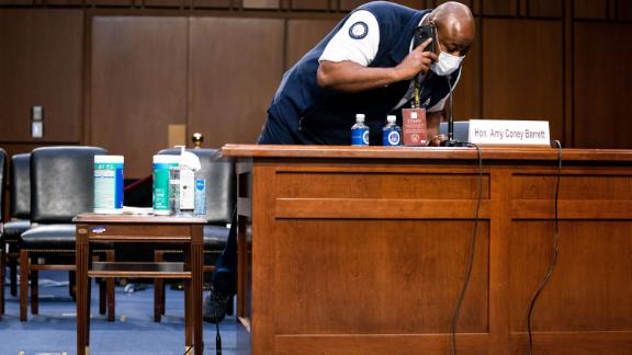 A staffer adjusts Barrett's microphone on October 14. There were technical difficulties with the hearing room's audio system, causing a couple of delays.