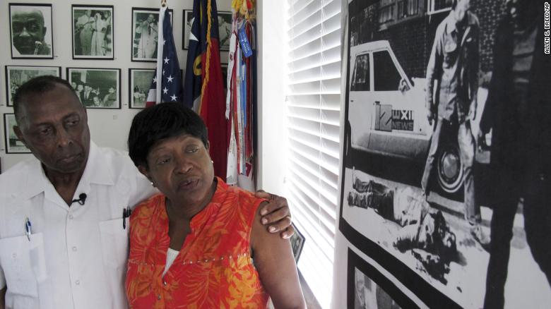 Rev. Nelson Johnson and his wife, Joyce, stand beside a 1979 photo of the Greensboro Massacre.