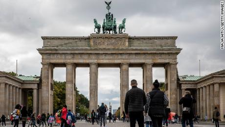 Tourists walk at the Brandenburg Gate in Berlin on Tuesday, as the city's businesses fight curfew orders in the courts.
