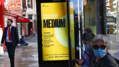 Commuters wearing masks at a bus stop near a poster showing Covid's local alert level were Medium in London on Thursday, before it rose to high on Saturday.