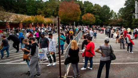 Hundreds of people wait in line for early voting on Monday, Oct. 12, 2020, in Marietta, Georgia.