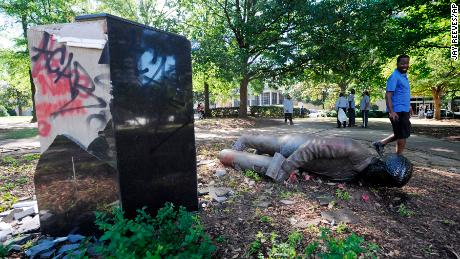A man walks past a toppled statue of Charles Linn, a city founder who was in the Confederate Navy, in Birmingham, Alabama on June 1, 2020.