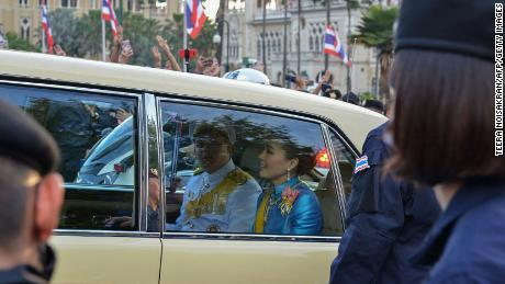 Thailand's Queen Suthida (C) and Prince Dipangkorn Rasmijoti (centre L) react inside a royal motorcade as it drives past a pro-democracy rally in Bangkok on October 14, 2020.
