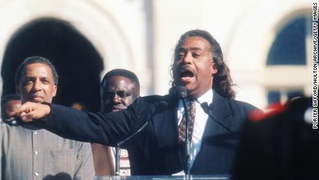 Reverend Al Sharpton speaks to the crowd while a member of the Nation of Islam stands guard at the Million Man March October 16, 1995 in Washington, DC.