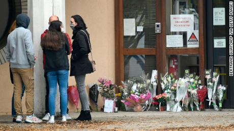 People stand at the flowers displayed at the entrance to the school in Conflans-Saint-Honorine.