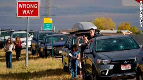 Onlookers gather at the overlook along Highway 36 to watch a smoke plume grow as several wildfires burn in northern and western Colorado, sending smoke on to the eastern plains, Saturday, October 17, 2020, near Boulder, Colorado.