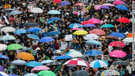 Des manifestants portant des masques faciaux se rassemblent avec leurs parapluies lors d'une manifestation dans la province de Nonthaburi.