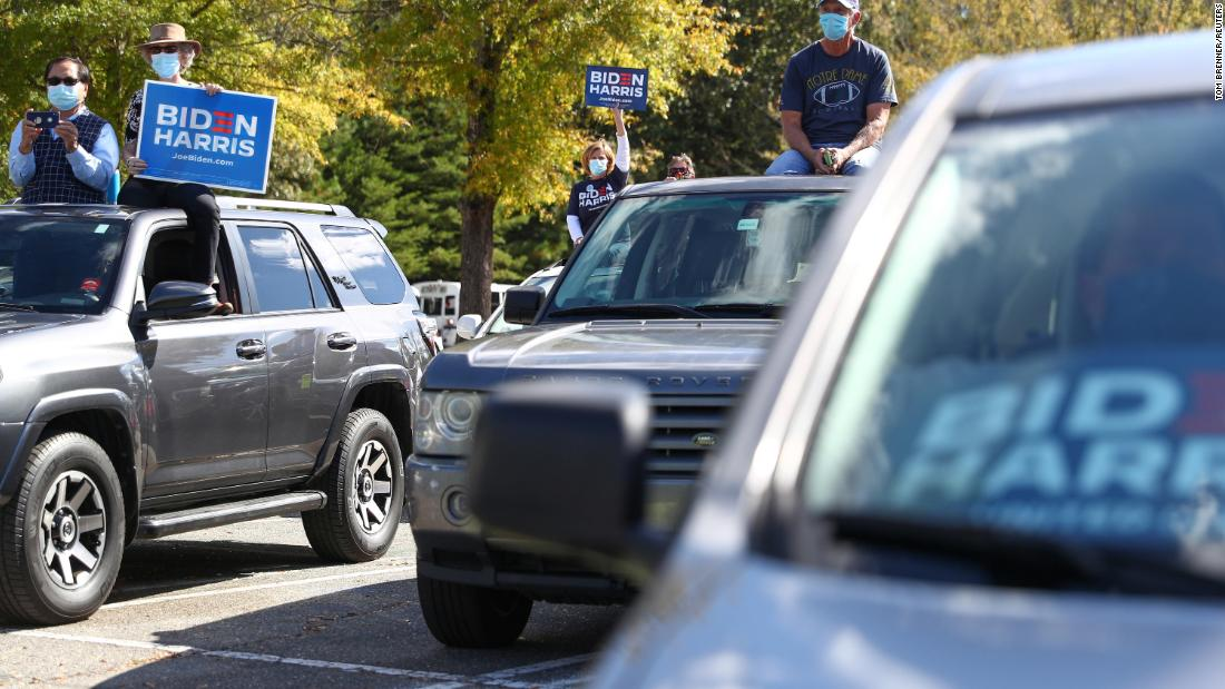 Attendees look on from their vehicles as Biden delivers remarks in Durham.