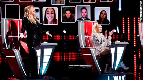 "(From left) Kelly Clarkson and Gwen Stefani, joined by a virtual audience, cheered during the so-called ""blind auditions"" of ""The Voice."""