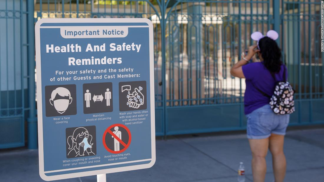 """A """"Health and Safety Reminders"""" sign is displayed outside the closed gates of California Adventure theme park, part of the Disneyland Resort, in Anaheim, California on Sept. 30, 2020."""
