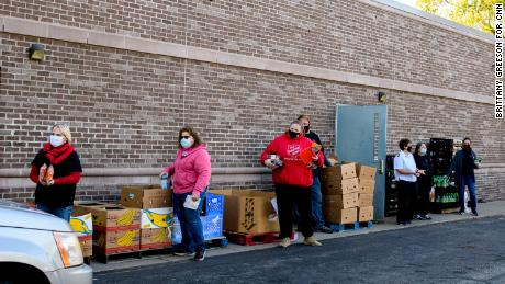 Volunteers assist cars picking up food donations outside the Salvation Army.