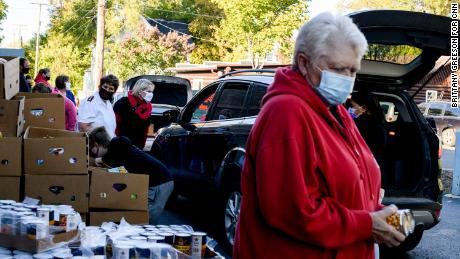 Volunteers assist cars picking up donated food outside the Salvation Army in Bay City, Michigan.