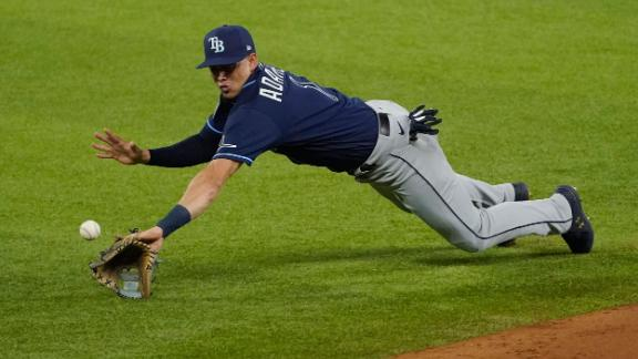 A ground ball hops over the outstretched glove of Rays shortstop Willy Adames.