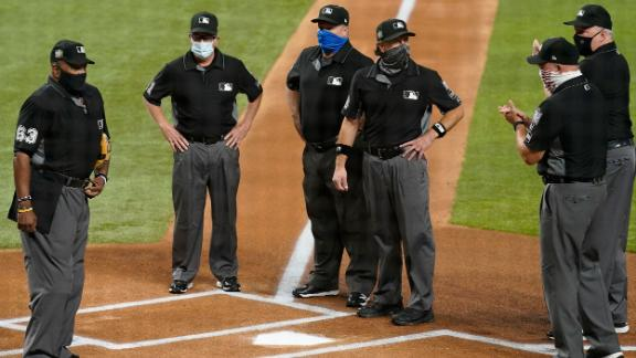 The umpire crew, all wearing masks due to coronavirus protocols, stands at home plate before Game 1.
