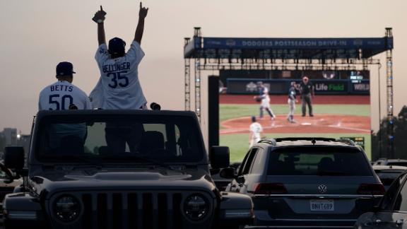 Mike Kim and Jacob Zelaya cheer from their car while watching the game outside Dodger Stadium in Los Angeles. Due to the coronavirus pandemic, Major League Baseball decided to play all World Series games at a neutral site in Arlington, Texas.