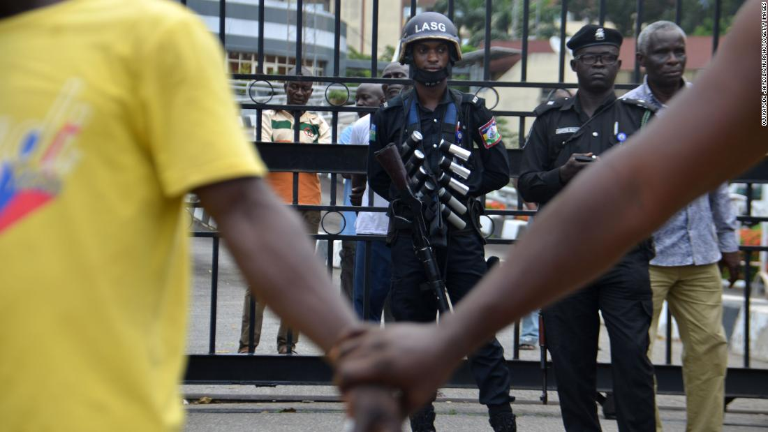 Protesters hold hands in front of police officers during a peaceful demonstration at the Alausa Secretariat.