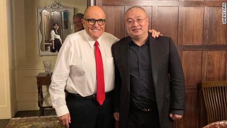 This photo appears to capture the reflection of virologist Li-Meng Yan in the mirror behind the two men in the foreground: Wang DingGang, board chair of the Rule of Law Society, and former New York City Mayor Rudy Giuliani. Bannon's image can also be seen in the photo.