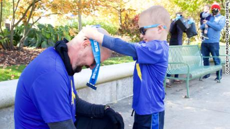 Kolt Codner's son awards him with a medal after completing his marathon to raise money for Akron Children's Hospital.