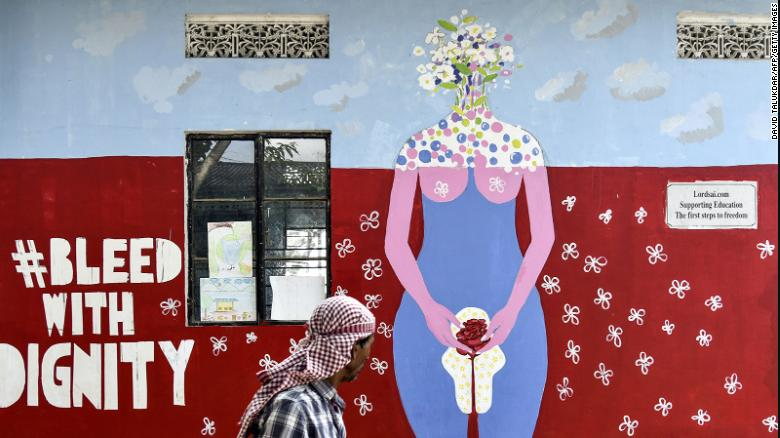An Indian man looks on as he walks along a wall painting about female menstruation at the school for underprivileged children, Parijat Academy, on the Menstrual Hygiene Day in Guwahati on May 28, 2019.