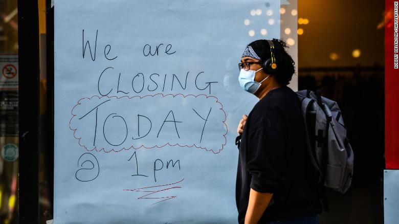 """A handwritten sign on a window of a shop announces its closure in Swansea city centre, south Wales, a day before the """"fire-break"""" lockdown comes into force."""