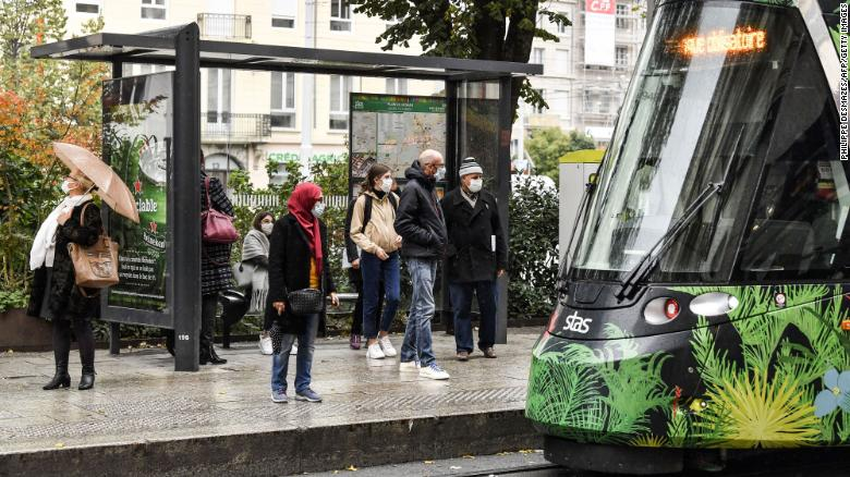 People wearing protective face masks  wait for a tram on October 22, 2020 in a street of Saint-Etienne, central eastern France.