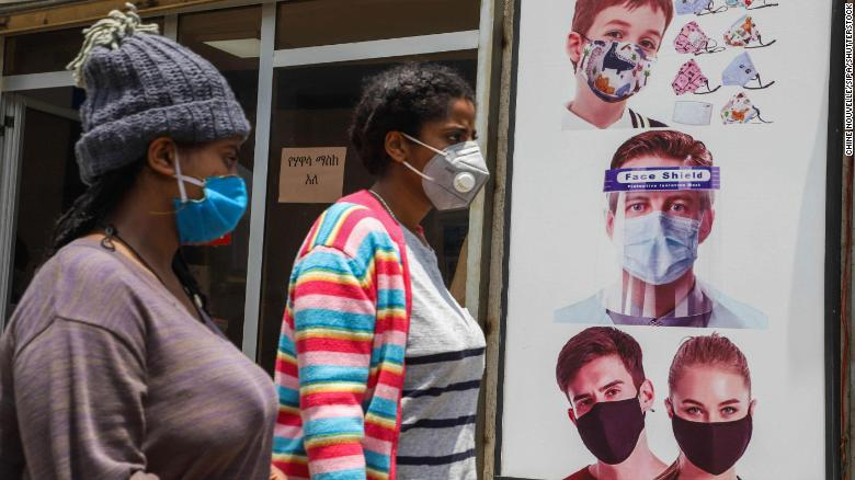 People wearing face masks walk past a poster promoting the use of face mask and face shield in Addis Ababa on August 21.