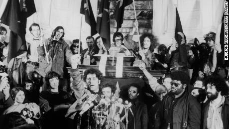 "American political activist Abbott ""Abbie"" Hoffman raises a fist from behind a bank of microphones during an unidentified rally in New York, late 1960s."