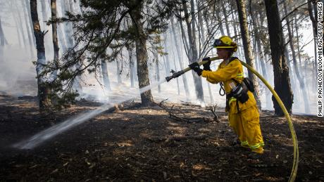 A firefighter waters a smoldering fire during the Diamond Fire in South San Francisco, California, U.S., on Friday, Oct. 16, 2020. The punishing heat gripping California will continue into Friday as dry winds threaten to fan fires across the already charred landscape and trigger another round of power outages.