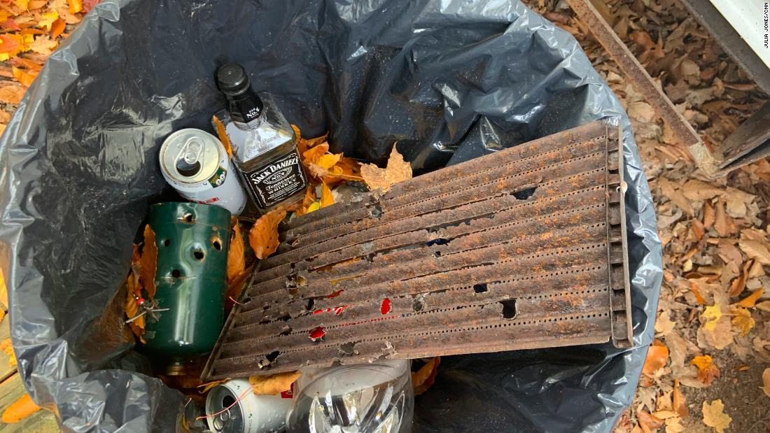 Cans, an empty bottle of whisky, and items with apparent bullet holes in a trash bin near Garbin's mobile home.